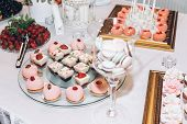 Delicious Sweets Cupcakes With Roses,pops And Candy On Table At Wedding Reception. Candy Bar. Tasty  poster