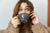 Photo of cheerful young woman 20s looking on camera with exciting look and drinking cup of tea at ho poster