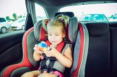 Blondy Baby Girl Fastened With Security Belt In Safety Car Seat And Plaing With Toy. Child In Auto B poster