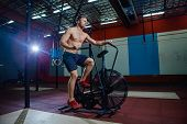Fit Young Man Using Exercise Bike At The Gym. Fitness Male Using Air Bike For Cardio Workout At Cros poster