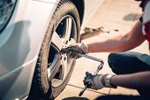 Tire Maintenance, Damaged Car Tyre Or Changing Seasonal Tires Using Wrench. Changing A Flat Car Tire poster