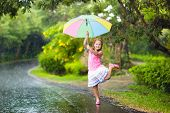 Kid Playing Out In The Rain. Children With Umbrella Play Outdoors In Heavy Rain. Little Girl Caught  poster