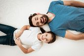 Adult Happy Bearded Man With Cute Little Daughter Lies On Bed In Mattress Store. Testing Softness Of poster