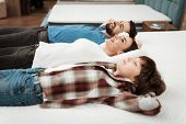 Young Happy Couple With Cute Little Boy Lies On Bed In Mattress Store. Family Checking Softness Of M poster
