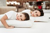 Smiling Little Girl With Beautiful Mother Hugs Pillows In Store Of Orthopedic Mattresses. Testing So poster