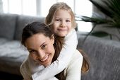 Happy Single Mother Laughing Piggybacking Little Girl At Home, Smiling Mom And Daughter Having Fun P poster