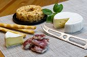 Cheese Appetizer Selection Or Cheese And Wine Party Table. Brie Cheese, Bread Sticks And Salami Is G poster