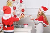Kids In Santa Hats Decorating Christmas Tree. Family Tradition Concept. Children Decorating Christma poster