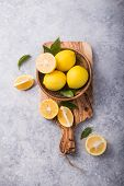Lemons. Yellow Lemons. Fresh Lemons. Fresh Lemons In Wooden Bowl With  Leaves On Grey Stone  Backgro poster