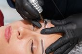 The Master Applies An Eyebrow Mask To The Client Using A Tattoo Machine. Permanent Eyebrow Makeup Pr poster