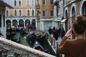 Beautiful Girl Traveler Photographs The Streets And Canals Of Venice On Her Smartphone. Warm Autumn  poster
