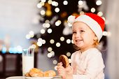 Treat For Santa. Adorable Little Girl Preparing Milk And Cookies On Christmas Eve, Empty Space poster