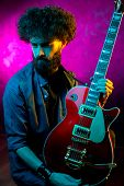 Close-up Photo Of Hipster Man With Red Guitar In Neon Lights. Rock Musician Is Playing Electrical Gu poster
