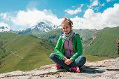 Young Female Sitting On The Peak Of Mountains. View Of Mountain Snowy Peaks Kazbek, Stepantsminda, T poster