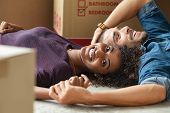 Happy multiethnic couple smiling while lying on floor near cardboard boxes. Portrait of african woma poster