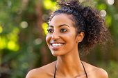 Smiling woman in swimsuit bikini looking away and smiling. Carefree young african american girl in b poster