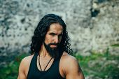 Young Stylish Man With Determined Character. Strong Confident Man With Long Wavy Dark Hair And Beard poster