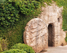 stock photo of empty tomb  - The entrance of a replica of the tomb where Jesus was buried with the stone rolled away - JPG