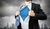 picture of transformation  - Image of young businessman showing superhero suit underneath his shirt standing against city background - JPG