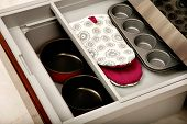 pic of saucepan  - A sliding kitchen drawer containing saucepans oven mitts and a muffin tin - JPG