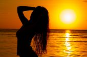 stock photo of rough-water  - fine silhouette of the girl against a solar decline - JPG
