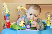 stock photo of teething baby  - Portrait of a cute 6 month old teething baby boy or girl biting a plastic toy in a walker of bouncer - JPG