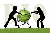 stock photo of caddy  - silhouette of two young women trying to monopolize a shopping caddy with a huge green bio apple - JPG