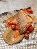 Seabass fillet cooked in Sicilian way with tomatoes, olives and courgette mash