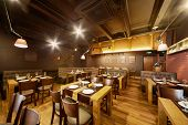 pic of public housing  - Interior of room in restaurant with wooden furniture and walls of red bricks - JPG
