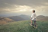 foto of pedal  - little child pedaling a bicycle in the mountain - JPG