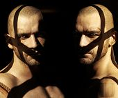 stock photo of shaved head  - Powerful fine art portrait of two twin male models in darkness with shadows and abstract elements obscuring their faces - JPG