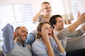 foto of indoor games  - Cheerful group of friends watching football game on tv - JPG