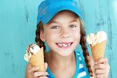 stock photo of unhealthy lifestyle  - Portrait of 7 years old kid girl eating tasty ice cream over blue - JPG