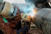 stock photo of pipe-welding  - Welder at Work on Outdoor Pipeline Project - JPG