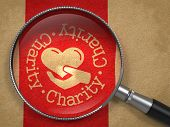 stock photo of glass heart  - Magnifying Glass with Charity Word Written Arround Icon of Heart in the Hand on Old Paper with Red Vertical Line Background - JPG