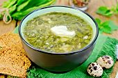 pic of sorrel  - Green soup of sorrel nettle and spinach in a bowl quail eggs bread pepper against a wooden board - JPG