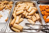 stock photo of chafing  - a lot of spring rolls in the food warmer of a self service restaurant - JPG