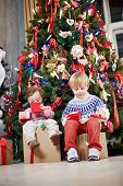 Little boy and little girl sit on big cardboard gift boxes under Christmas tree, holding open gift b
