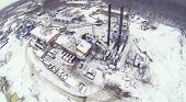 Industrial area with machines and crane at winter day. Aerial view