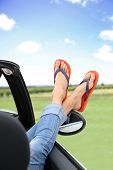 stock photo of car-window  - Closeup of feet with flip flops showing by car window - JPG