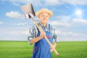 Mature agricultural worker holding shovel in field