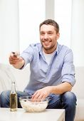 home, technology and entretainment concept - smiling man with beer, popcorn and tv remote control at