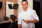 foto of barber  - Handsome young Latin barber loving his job and smiling