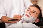 foto of razor  - Closeup of a young man getting a close shave at a barber shop - JPG