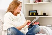young woman sitting on sofa and using digital tablet