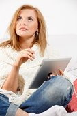 Thinking attractive woman on sofa using her tablet