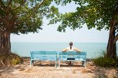 stock photo of sitting a bench  - Young woman sitting on bench facing the sea in Thailand - JPG
