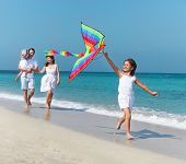 picture of kites  - Happy young family with flying a kite on the beach - JPG