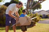 image of aeroplane  - son and dad playing with toy aeroplane in the garden at home having fun together and smiling - JPG