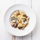 foto of clam  - Seafood pasta with clams Spaghetti alle Vongole on white wooden background - JPG